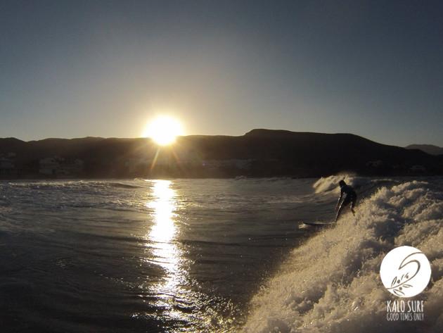Surfer in sunset wave in Crete