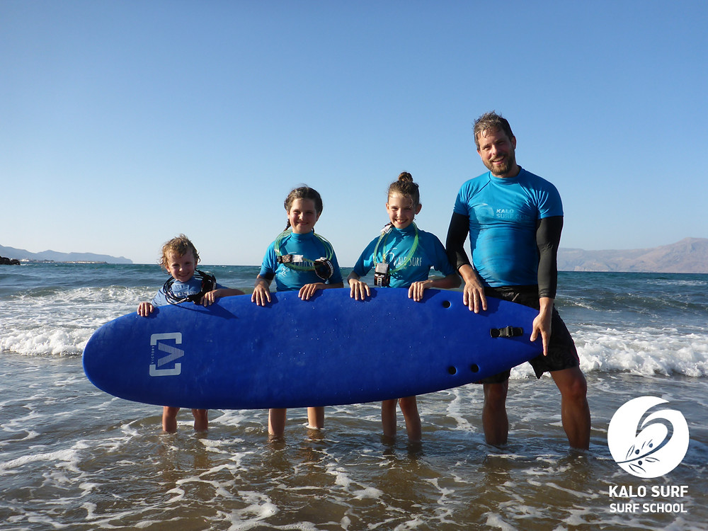 family holding a surfboard in Crete