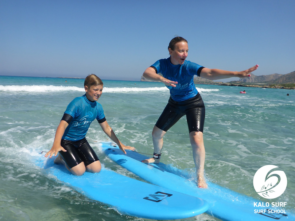 mum and son surfing together on a wave