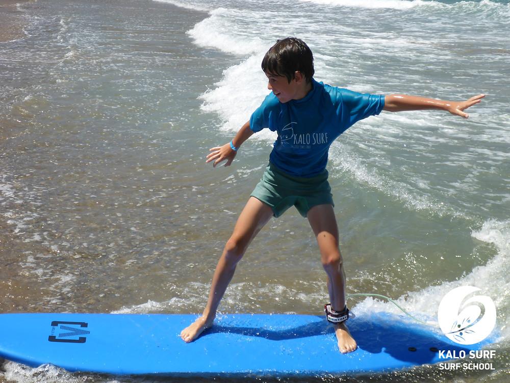 kid surfer surfing a wave surf lesson Greece