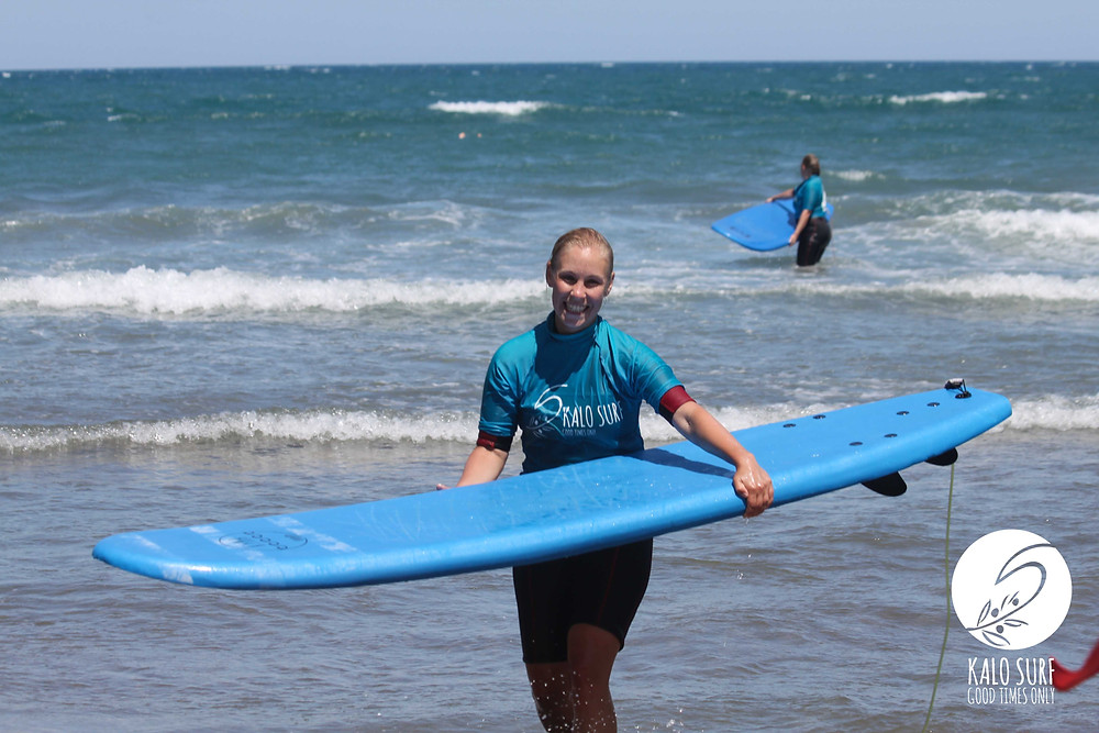 surf girl with surfboard at beach