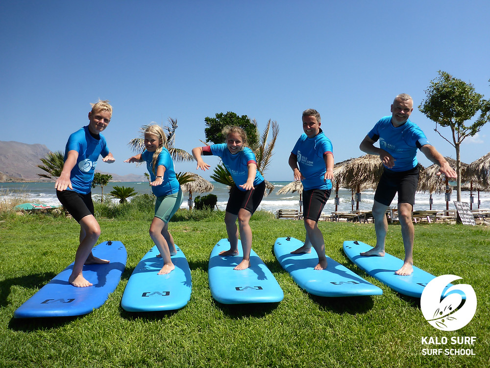 Family posing with surfboards for a group picture