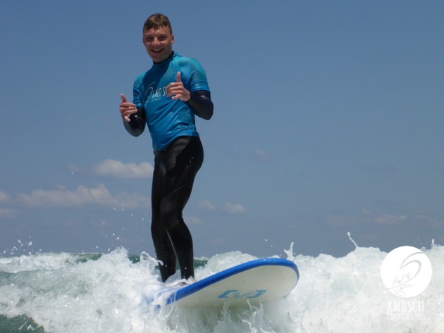 Surfer with shaka surfing waves in Crete