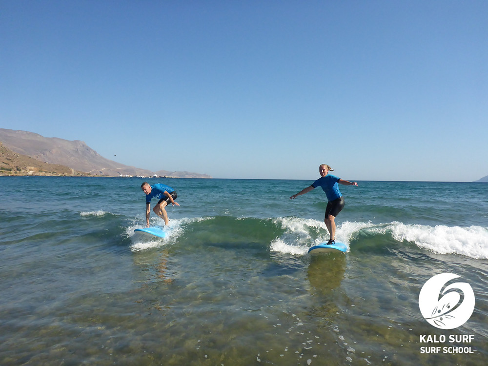 Zwei Surfer surfen eine Welle gemeinsam