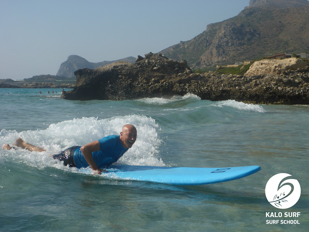 surfer gliding on a surfboard in Falasarna Crete