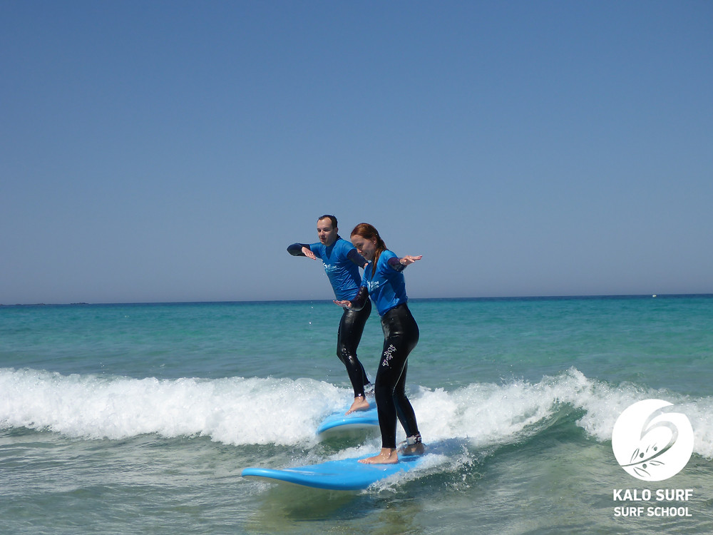 a couple riding a wave together