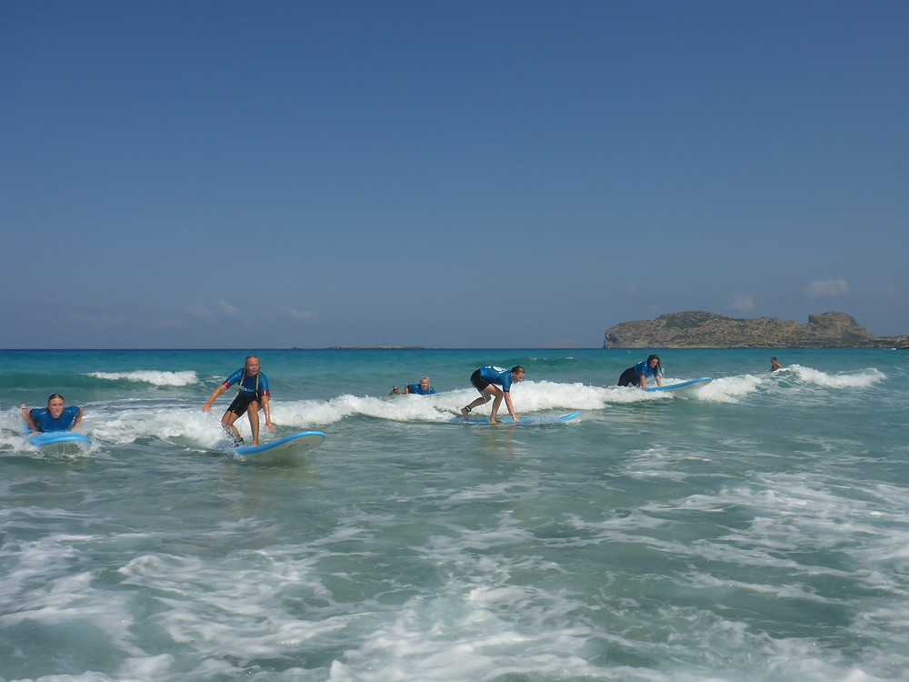 Surfer girls catching waves together in Crete