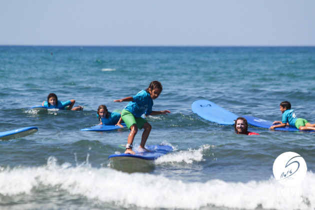 Small kid surfs waves in Crete