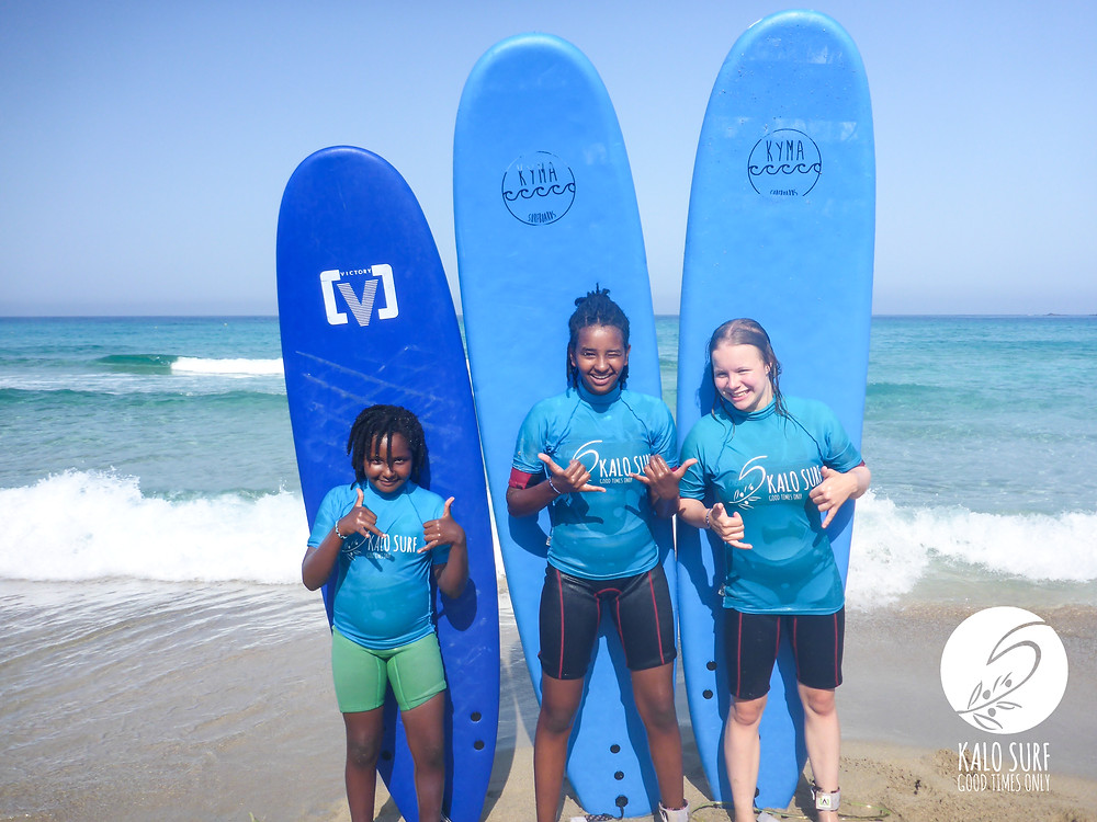surfer girls group picture with surfboards