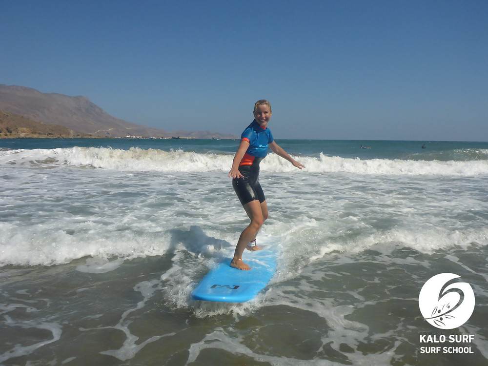 smiling while riding a wave in Crete