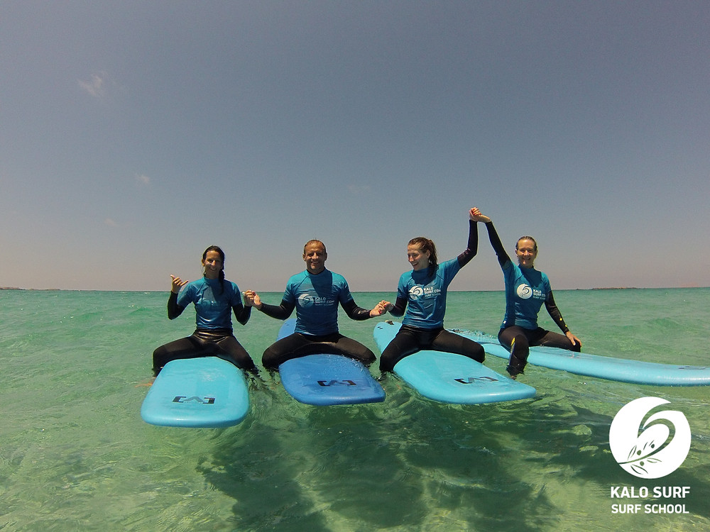 group photo surfboards crystal clear waters