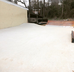 Skate slab with hip ramps and rail