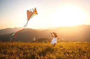 happy child girl running with a kite at