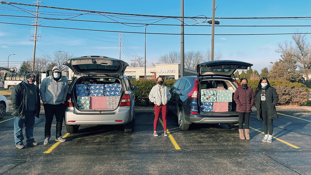 Two men (Ray Galarza and Esteban Diaz) standing next to a large minivan with gifts assembled by SOS staff. To the right of them is another van full of packaged gifts with Faith Massey, Jasmin Mundi, and Parveen Mundi. It is a bright sunny day.