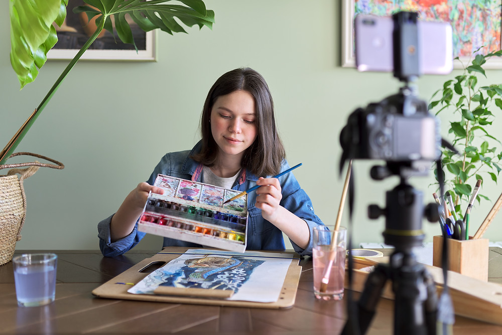 A young girl sitting at a desk, holding up a painting pallet in one hand, and a brush in the other. On the table is a piece of paper covered in paint on top of a wooden board. There is a camera on a tri-pod recording her.