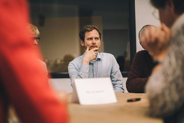 Dennis Hebbelmann am Tisch sitzend in einem Workshop
