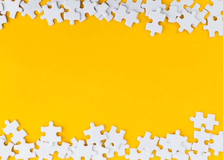 Pieces of jigsaw puzzle on yellow backgr