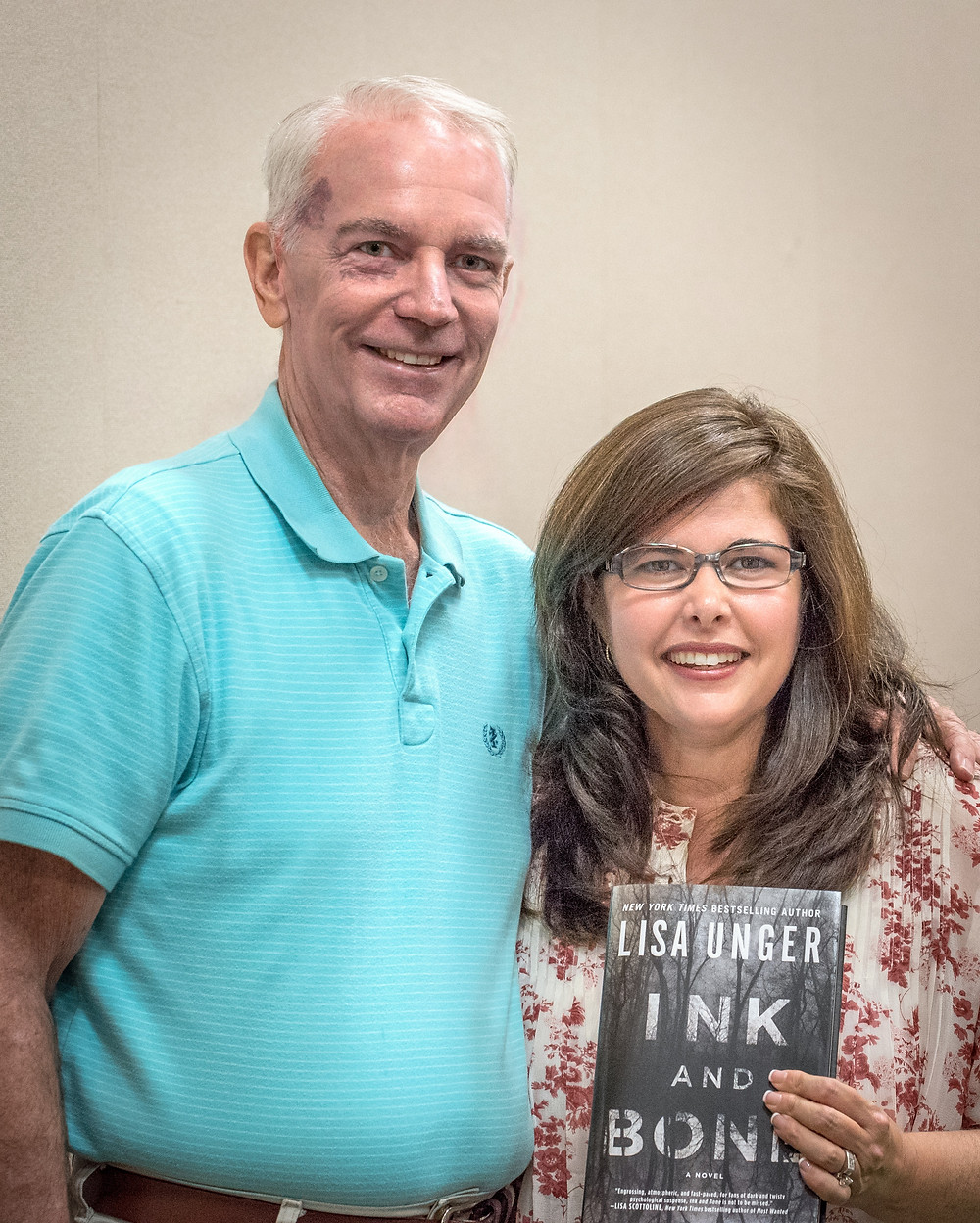 Lisa Unger, standing with SFWr President Jerry Keane, displays her lasts novel.