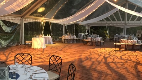 Swags of white fabric and cl;ear bulb miniature white lights thoughout the ceiling of clear top tent, breakup patterns projected on dance floor in soft amber color tones