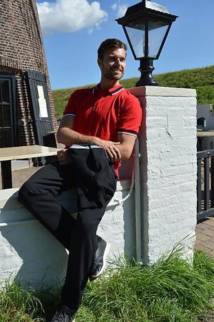 Man draagt een Silvermedal trainingspak met een rode polo, zwarte vest en zwarte trainingsbroek