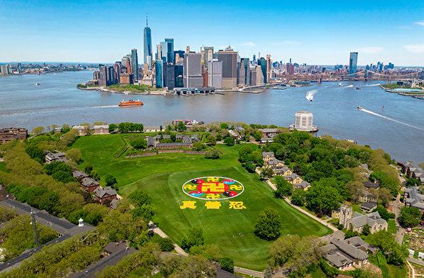 """2019年5月18日,来自全球的部分法轮功学员会聚纽约,在纽约总督岛排出""""法轮图形""""和""""真善忍""""三个大字,庆祝世界法轮大法日。(William Wang/新唐人电视台)"""