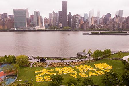 """2017年5月13日,法轮大法弟子在纽约联合国总部对面甘纯公园(Gantry Park)举行大型排字活动,排出""""大法洪传25周年""""。(戴兵/大纪元)"""