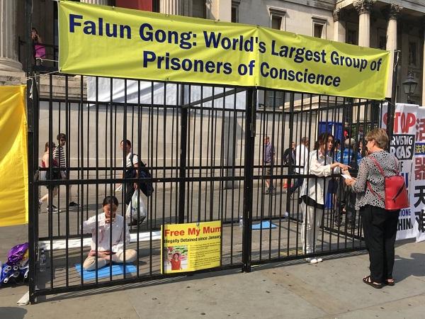"""""""有类似我母亲这种遭遇的人在中国太多了。""""在特拉法加广场,晓童(左)在演示酷刑的铁笼内无声讲述着中国正发生着的迫害。(陆漫/大纪元)"""
