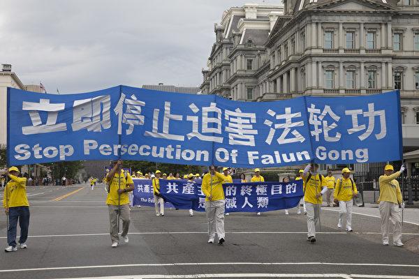 """2018年6月20日,全球部分法轮功学员聚集在美国首府华盛顿DC举行反迫害大游行。图为要求""""立即停止迫害法轮功""""的大型横幅。(季媛/大纪元)"""