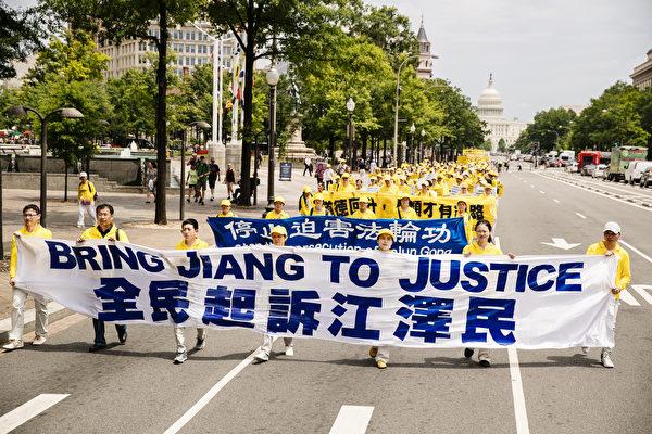 """2018年6月20日,全球部分法轮功学员聚集在美国首府华盛顿DC,举行反迫害集会游行。图为游行队伍中""""全民起诉江泽民""""的横幅。(爱德华/大纪元)"""