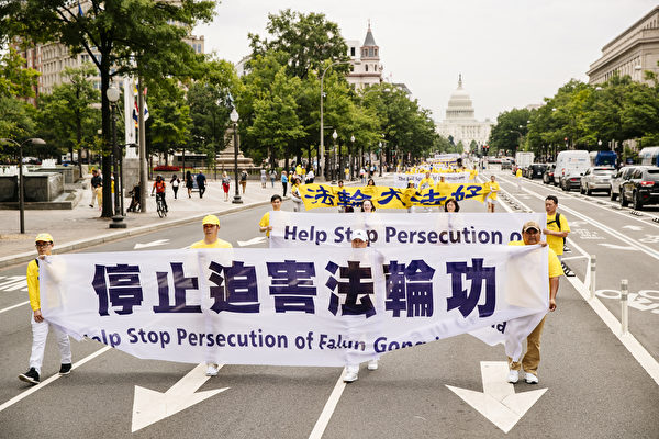 2018年6月20日,全球部分法轮功学员聚集在美国首府华盛顿DC,举行反迫害集会游行。图为法轮功学员以大型横幅要求中共停止迫害法轮功。(爱德华/大纪元)