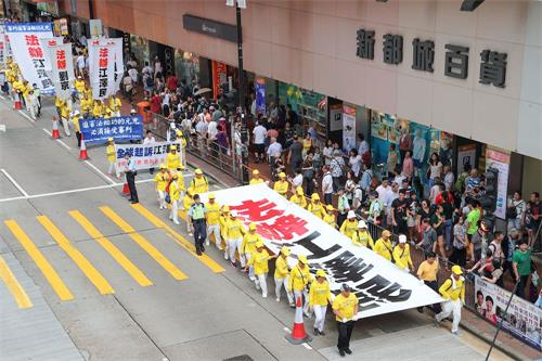 约一千名法轮功学员7月22日在港岛区举行反迫害十九周年集会游行,呼吁停止迫害、法办元凶。游行队伍中大小横幅展示中共迫害法轮功的真相,震撼许多大陆游客。(明慧网)