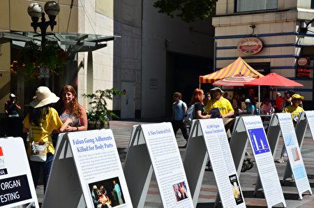 2018年7月21日,大西雅图地区的部分法轮功学员来到西雅图市中心西湖公园集会,纪念法轮功反迫害19周年。图为法轮功学员和民众讲真相。(马明/大纪元)
