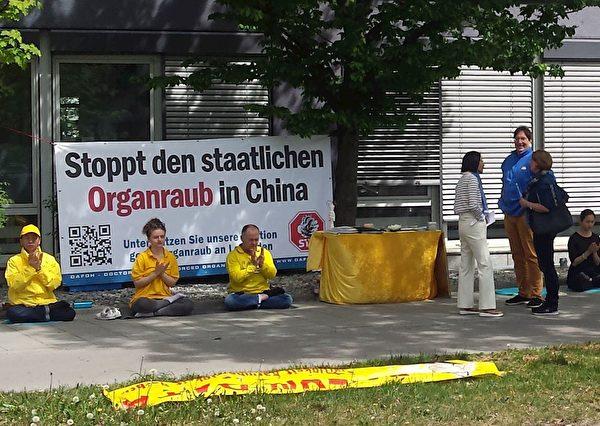 4月25日,慕尼黑中领馆前,法轮功学员抗议中共迫害。(明慧网)