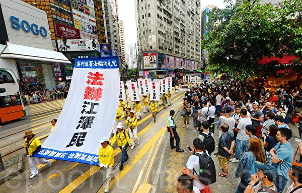 来自各国上千名法轮功学员22日举行反迫害19周年游行,从北角经过市区,最后到中联办,途中吸引许多民众观看。(宋碧龙/大纪元)