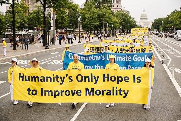 """2018年6月20日,全球部分法轮功学员聚集在美国首府华盛顿DC,举行反迫害集会游行。图为法轮功学员持""""Humanity's Only Hope is to improve Morality""""的英文横幅,告诉人们道德回升人类才有出路。(爱德华/大纪元)"""