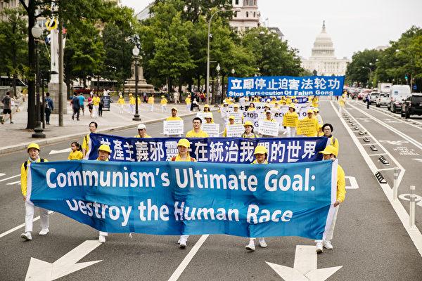 """2018年6月20日,全球部分法轮功学员聚集在美国首府华盛顿DC,举行反迫害集会游行。图为法轮功学员以横幅告诉人们""""共产主义邪灵正在统治我们的世界""""。(爱德华/大纪元)"""