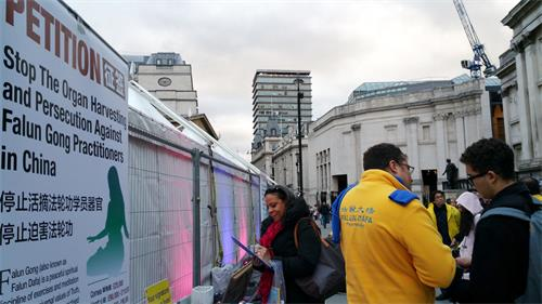 二零一八年十月二十七日,退休伦敦女士马琳(Marlyn,左)在特拉法加(Trafalgar Square)广场签名支持法轮功反迫害。(明慧网)