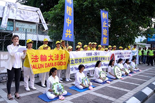 2018年7月20日,马来西亚法轮功学员来到中共使馆,在车水马龙的大路旁举行集会,悼念被中共迫害致死的法轮功学员。(朱利达/大纪元)