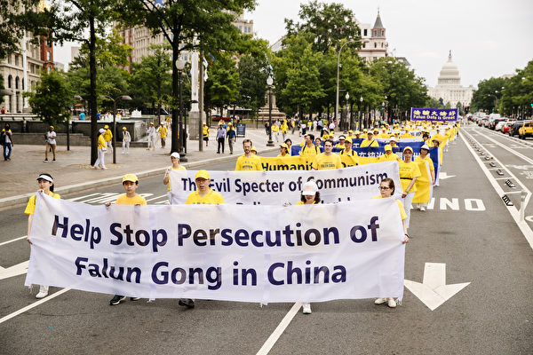 """2018年6月20日,全球部分法轮功学员聚集在美国首府华盛顿DC,举行反迫害集会游行。图为法轮功学员以英文横幅""""Help Stop Persecution of Falun Gong in China""""呼吁民众帮助制止在中国对法轮功的迫害。(爱德华/大纪元)"""