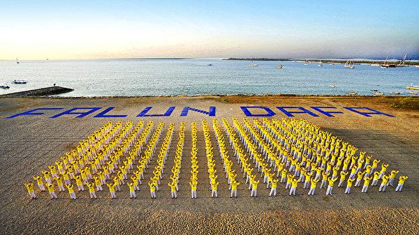 """2015年9月25日,印尼法轮大法修炼者在巴厘岛海滩排出""""FALUN DAFA""""巨大字形。(明慧网)"""