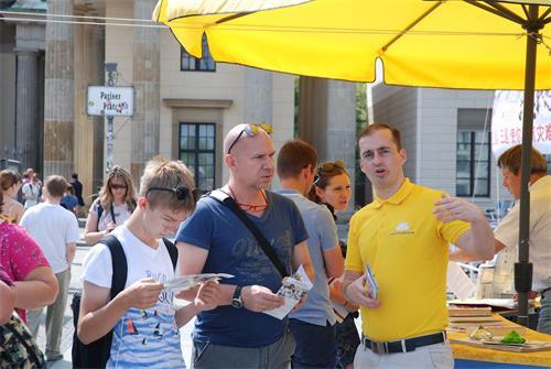 【明慧网二零一九年六月二十四日】(明慧记者雪莉德国柏林报道)二零一九年六月二十二日星期六中午,柏林法轮功学员一如既往在布兰登堡门前的巴黎广场上向各国游客和当地民众讲真相。当天艳阳高照,法轮功学员横幅高挂,吸引许多游客一看究竟。横幅前数十位学员一字排开,在祥和的音乐声中演示功法。布兰登堡门位于德国首都柏林的市中心,是柏林,也是德国的国家象征标志。