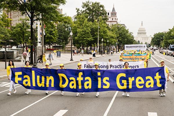 """2018年6月20日,全球部分法轮功学员聚集在美国首府华盛顿DC,举行反迫害集会游行。图为法轮功学员以大型英文横幅""""Falun Dafa is Great""""告诉人们法轮大法好。(爱德华/大纪元)"""