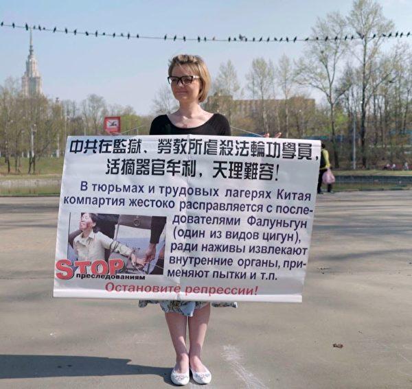 4月25日,莫斯科法轮功学员从早上10点开始了在中使馆前的单人抗议接力活动,一直持续到晚上10点。他们手举展板,坚定地站在中使馆门口,要求中共立即停止对法轮功的迫害。