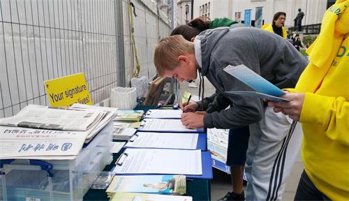 另一位第一次听闻法轮功真相的伦敦中学生签名支持法轮功学员反。(明慧网)