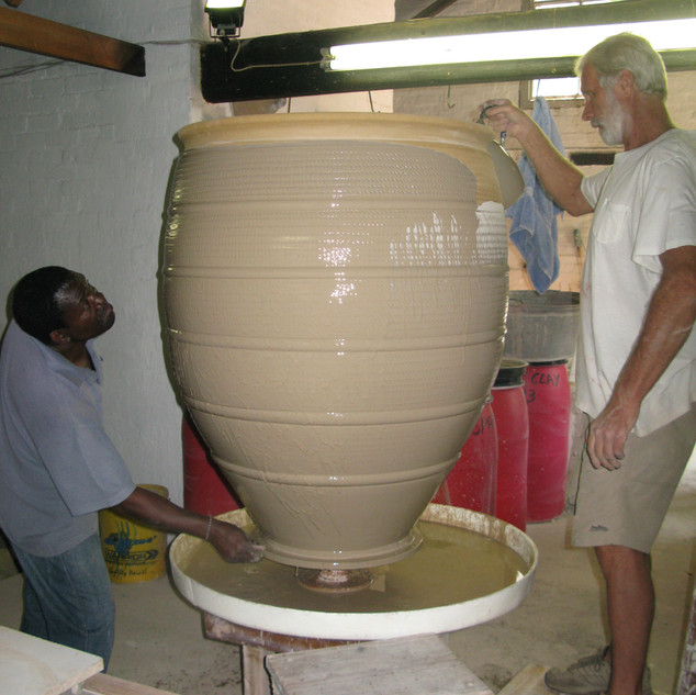 Digby pouring glaze on a large pot