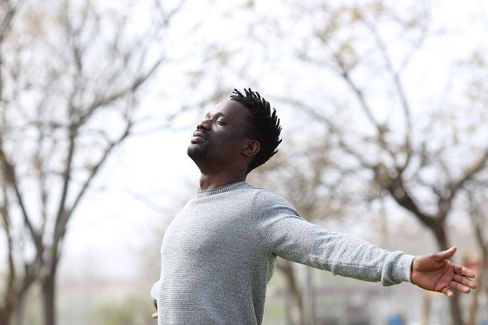 Satisfied black man breathing fresh air