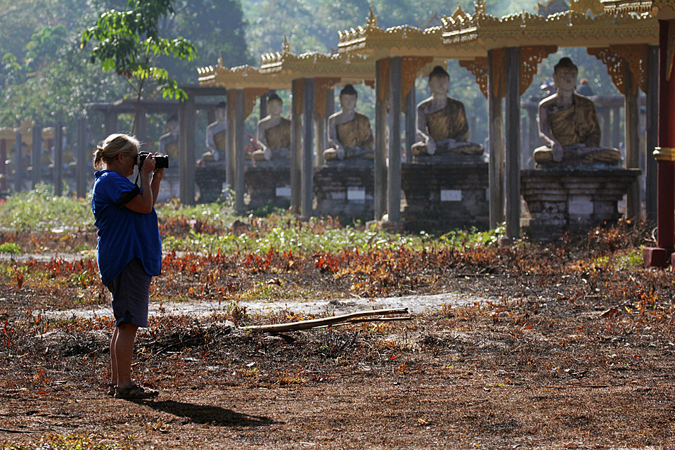 A traveller takes a moment to study the scene before taking her photograph - Myanmar.