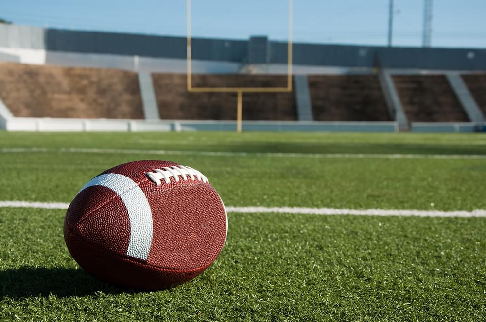 A football on the ground in an empty football stadium