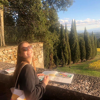 Tori smiling at the camera while using watercolor paints to paint the grape fields in Brolio, Italy.