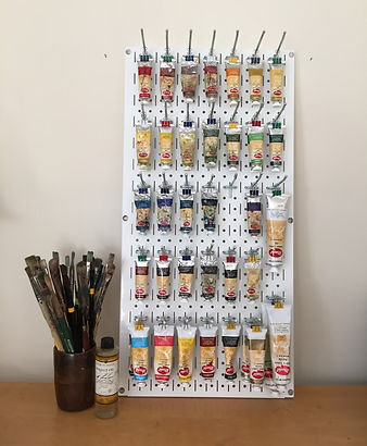 Oil painting supplies include several size brushes, tubes of Utrecht oil paints and walnut oil